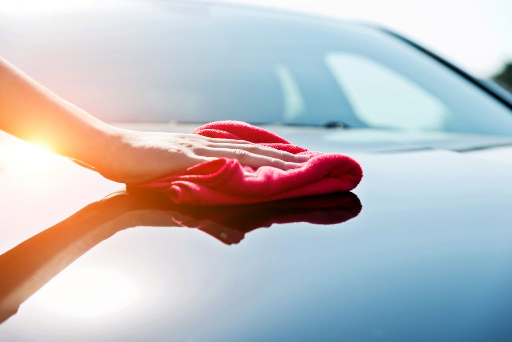 Woman hand drying the vehicle hood with a red towel
