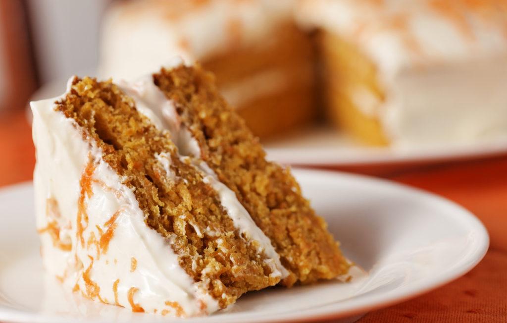 Homemade carrot cake dessert on white plate.