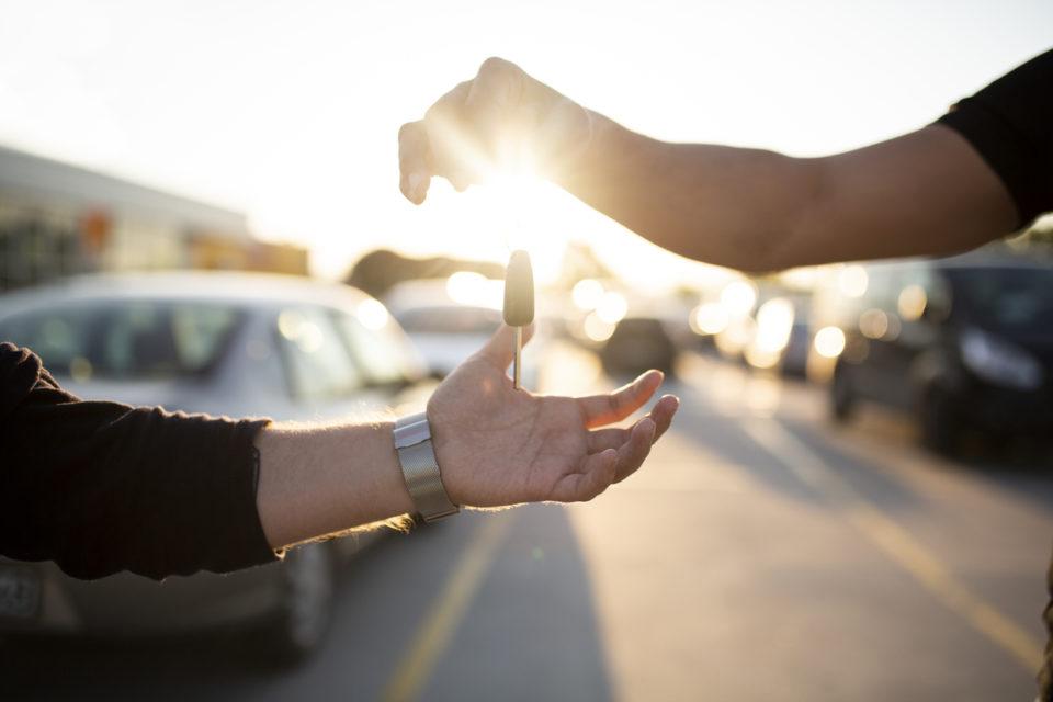 Salesman handing car key over to buyer