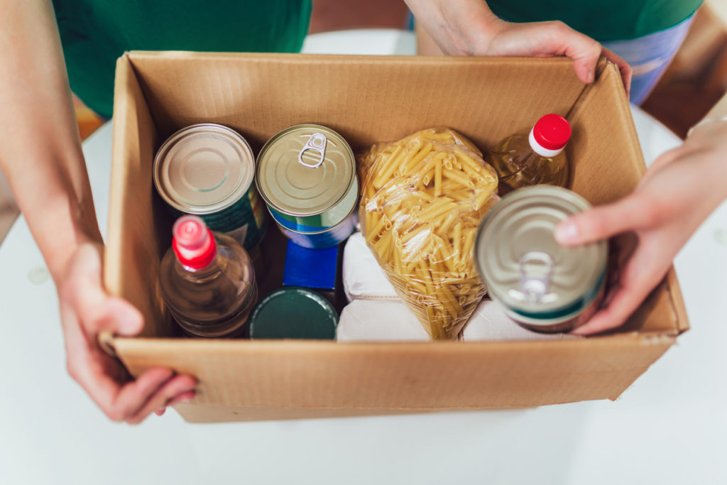 Volunteer with box of food.